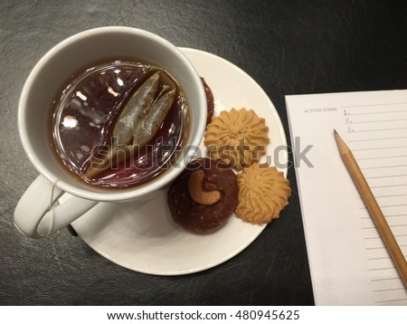 Hot tea in white cup and chocolate, vanilla cookies, put near pen on notebook, on black leather table.  Business & Seminar concept