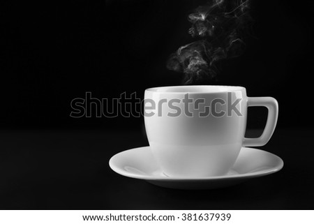 Hot tea in white cup on black background, close up - stock photo