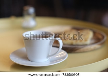 Hot tea in white glass placed on a yellow iron table in a coffee shop.