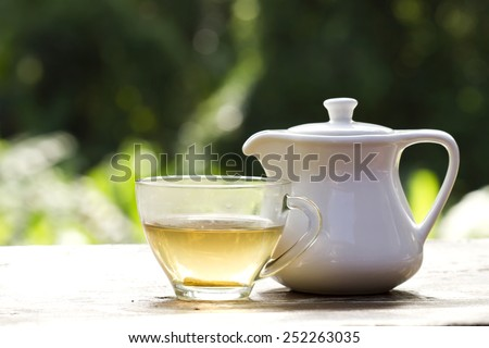 Hot tea or a cup of tea and white tea bowl on wooden table with room for refreshments - stock photo