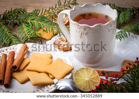 Hot tea with citrus, cinnamon, cloves and honey on a wooden table. - stock photo