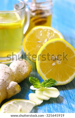 Hot tea with ginger,lemon,honey and mint in a glass on a blue table. - stock photo