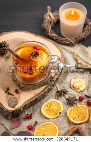 Hot tea with orange and cranberry on wooden board on black background