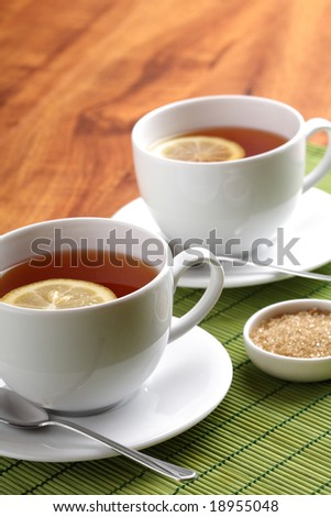 Hot teacup with lemon and sugar - stock photo