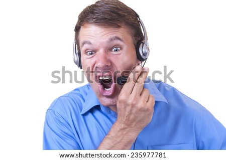 Hot tempered angry Caucasian man wearing blue collared shirt and communications headset holds mic and yells furiously on white background