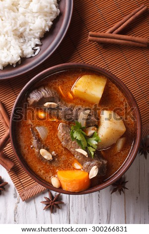 Hot traditional Thai beef massaman curry with peanuts and rice side dish close up. vertical top view - stock photo