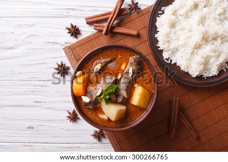 Hot traditional Thai beef massaman curry with peanuts and rice side dish. horizontal view from above - stock photo