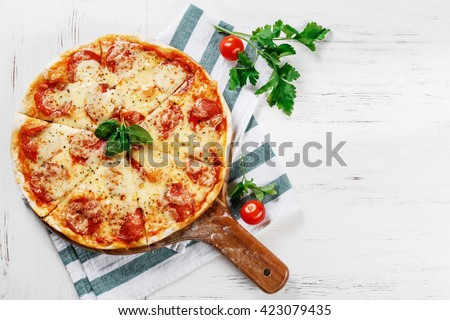 Hot true PEPPERONI ITALIAN PIZZA with salami and cheese. TOP VIEW Tasty traditional pepperoni pizza on board on white wooden table with decoration. Copy space for your logo. Ideal for commercial  - stock photo