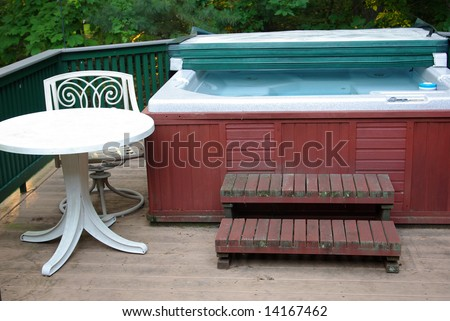 Hot tub with chair and table - stock photo