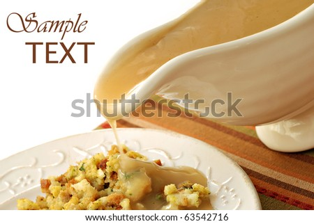 Hot turkey gravy being poured over plate of stuffing on white background with copy space. Slight motion blur on drip. - stock photo