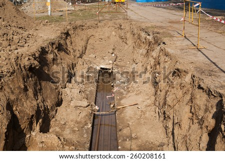 Hot water pipes breakage - open pit for repairing - stock photo