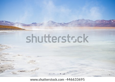Hot water ponds in geothermal region of the Andean Highlands in Bolivia. Frozen salt lake, distant mountain range and barren volcanos in the background. Roadtrip to the famous Uyuni Salt Flat. - stock photo