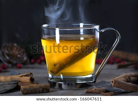 Hot  whiskey, rum, apple or brandy toddy cocktail drink with cinnamon set on rustic wood - stock photo