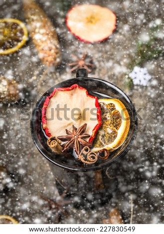 Hot wine punch on dark wooden background with fir branch and cone in snow - stock photo