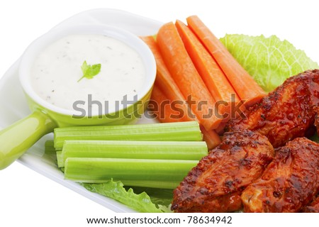 Hot wings served on a bed of lettuce, with fresh carrot and celery sticks.  A cool ranch dip for the vegetables, compliments the hot flavor of the wings.  Shot on white background. - stock photo