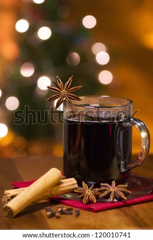 Hot winter drink in glass with spices and illuminated Christmas tree in the back ground. - stock photo