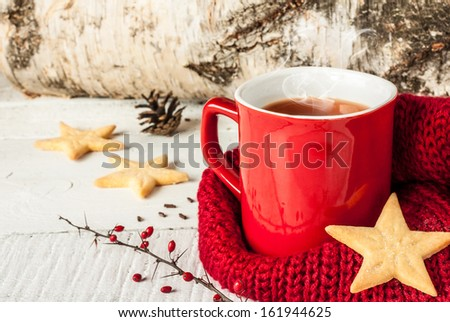 Hot winter tea in a red mug with star shaped christmas cookies and warm scarf - rural still life - stock photo