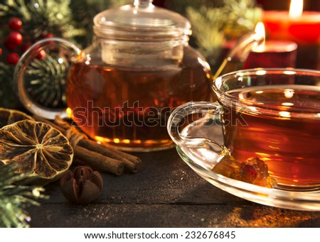 Hot winter tea with spices in glass cup and teapot on Christmas table decorated with conifer branches and candles, close up - stock photo