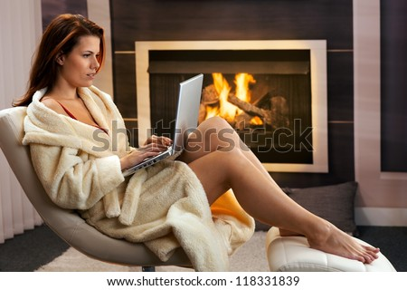 Hot woman sitting in bathrobe using laptop computer in front of fireplace, enjoying winter leisure. - stock photo