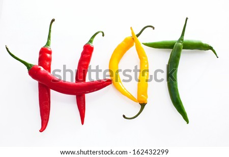Hot word made from red, yellow and green hot chili pepper on white background   - stock photo