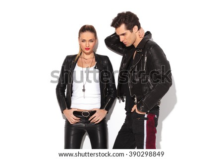 hot young couple in leather clothes, man with hands behind his neck and woman standing with hands on waist
