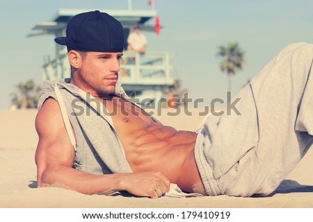 Hot young guy at the beach with very subtle retro toning - stock photo
