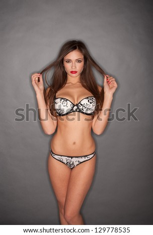 Hot young woman in black and white lingerie posing on grey background - stock photo