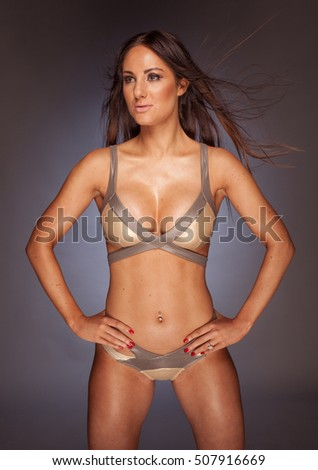 Hot young woman in gold elegant lingerie looking aside with hands on hips over gray wall background