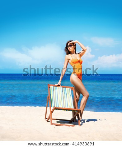 Hot, young woman with perfect legs posing on the beach nearby sun lounge.