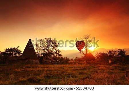 Hotair balloon and field at sunset - stock photo