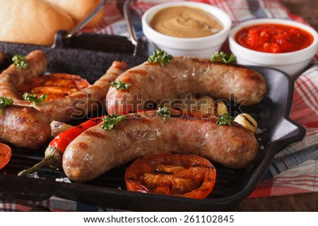 Hotdog Cooking: Grilled sausages, vegetables in a pan grill,  buns with sauce on the table close-up. horizontal