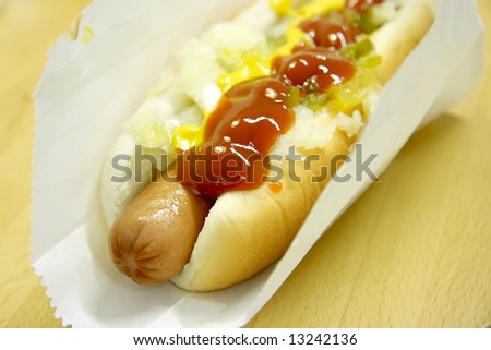Hotdog fastfood sausage in bun with condiments - stock photo