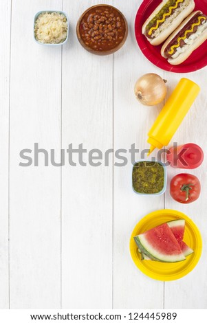 Hotdog sandwiches, watermelon slices  and condiments arranged in a table - stock photo