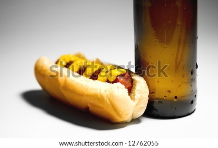 Hotdog with mustard and a cold beer - stock photo