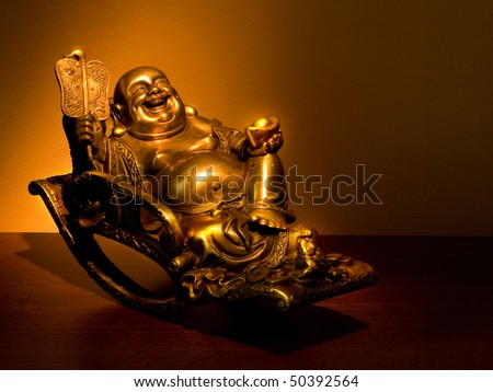 Hotei - chinese god of wealth, prosperity and happiness seating in the rocking-chair. Ancient figurine - stock photo