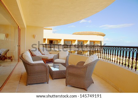 Hotel balcony with rattan armchairs and nice view - stock photo