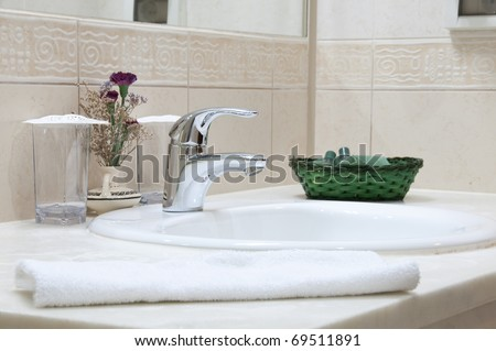 Hotel bathroom: sink, tap, towel and bathroom set - stock photo