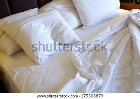hotel bed with crumpled sheets - stock photo