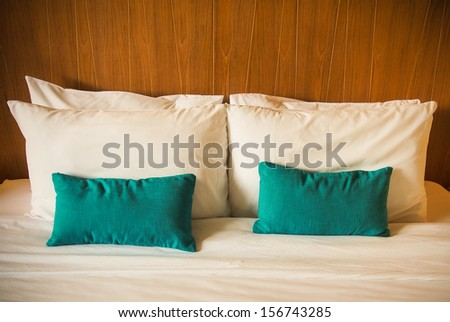 Hotel bed with white and blue pillows - stock photo