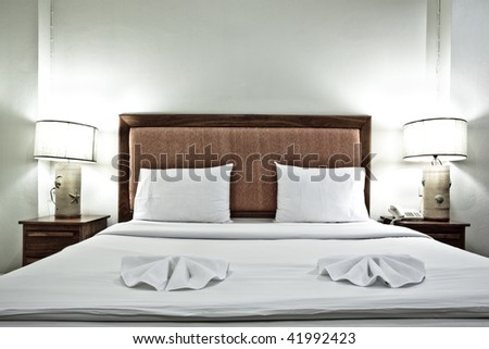 Hotel bedroom interior with pillows and lamps in evening