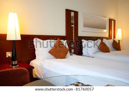 Hotel Bedroom interior with pillows and lights on side tables