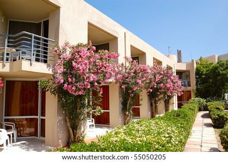 Hotel building decorated with beautiful flowers,  Crete, Greece - stock photo