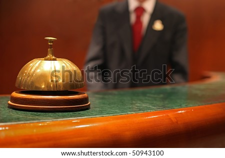 Hotel Concierge: bell on the reception front desk with waiter - stock photo