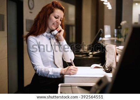 Hotel Concierge. Reception of hotel, desk clerk, woman taking a call and smiling. - stock photo