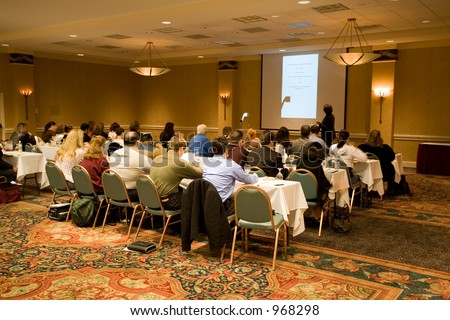 Hotel conference room full of people participating in the business training. - stock photo