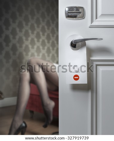 Hotel door with do not disturb icon and sexy female legs on the background; adultery concept - stock photo