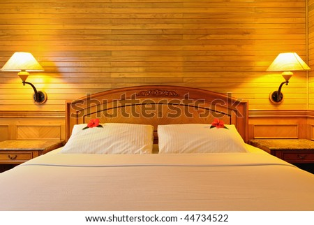 Hotel double bed with flowers on pillow, lighting lamps. Front view. - stock photo