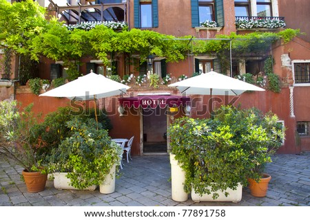 Hotel entrance of red hotel with green plants - stock photo