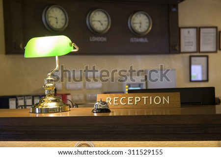 Hotel front desk with focus on reception sign. Made with shallow depth of field. - stock photo