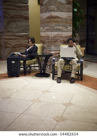 Hotel guests waiting in an upscale hotel lobby. - stock photo